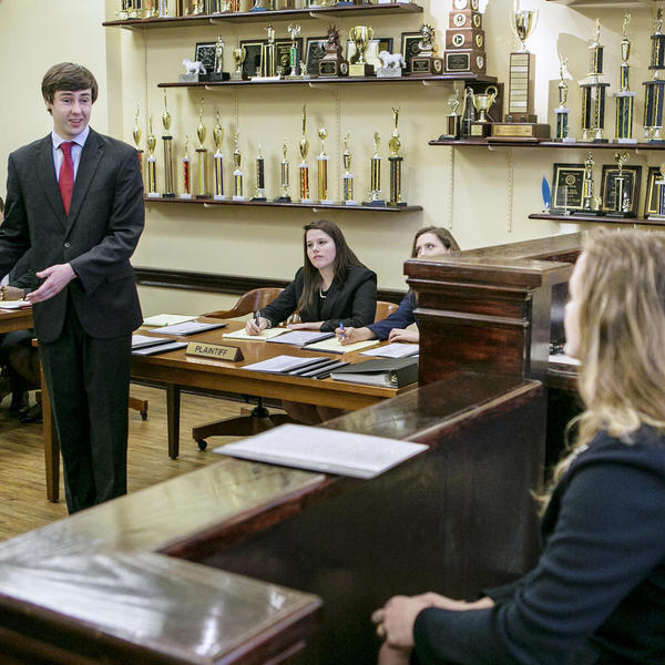 Young man in a suit gestures to evidence as opposing council and a judge look on.