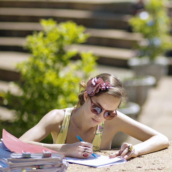 Young woman studying in the summer sun