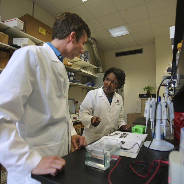 Two researchers in white coats stand at a lab table reviewing notes.
