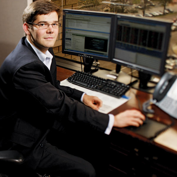 A young man in a suit sits at a computer, looking back at the camera.