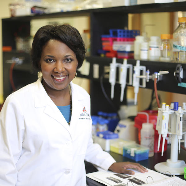 An african american professor in her lab coat stands at a lab table.