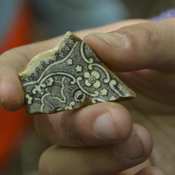 A fragment of a clay pot, intricately decorated with black line drawings.