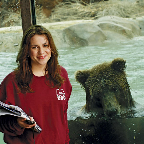 A young woman with a clipboard stands in front of a grizzly bear.