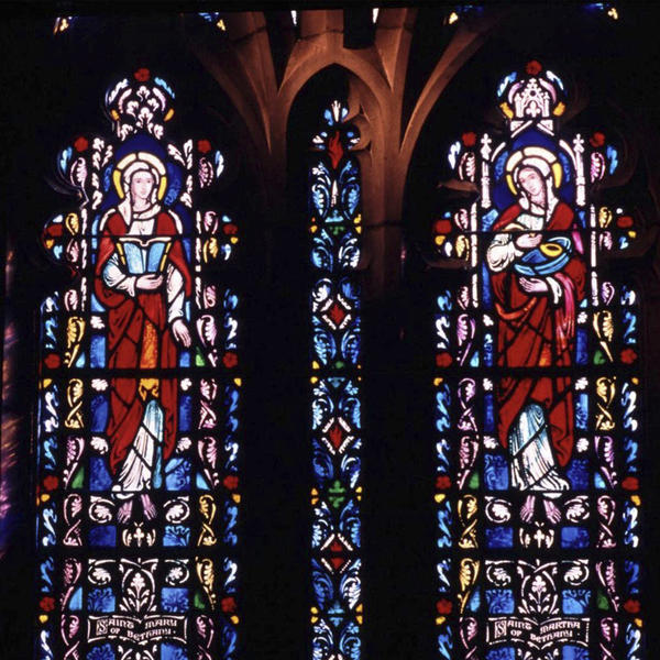 Two panels of stained glass featuring Mary Magdalene and Mary, mother of Jesus on a stone chapel wall