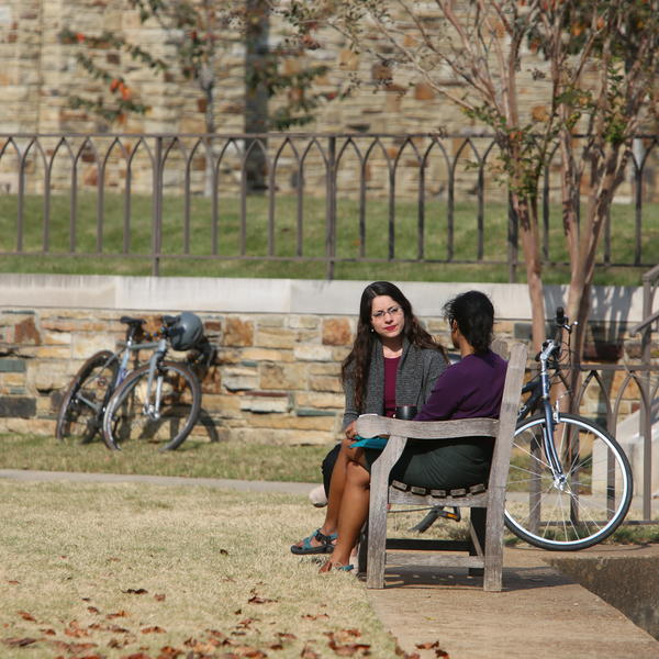 Students confir on a bench in an open quad.