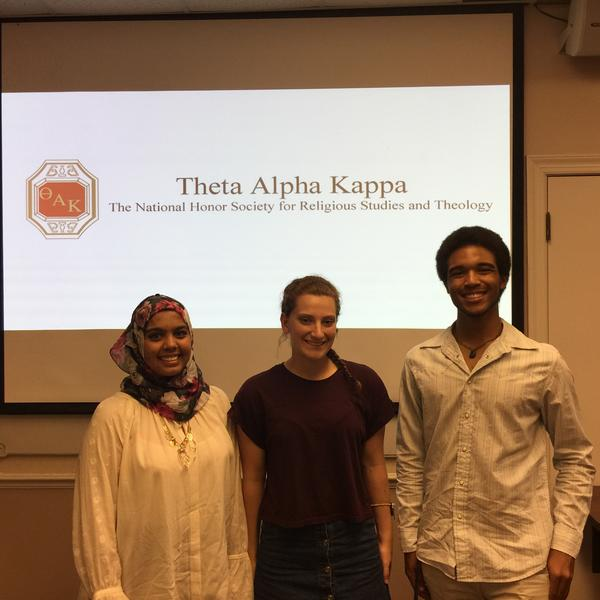 Three students stand in front of a projection screen reading Theta Kappa Alpha