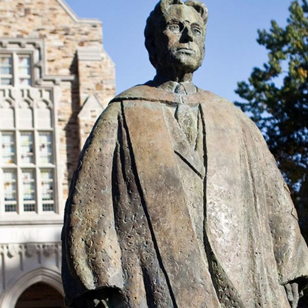 A bronze statue of a male professor in academic regalia looking off into the sunset.