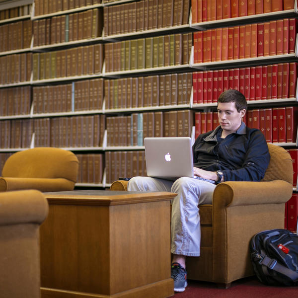 A student sits with his laptop in front of shelves of periodicals