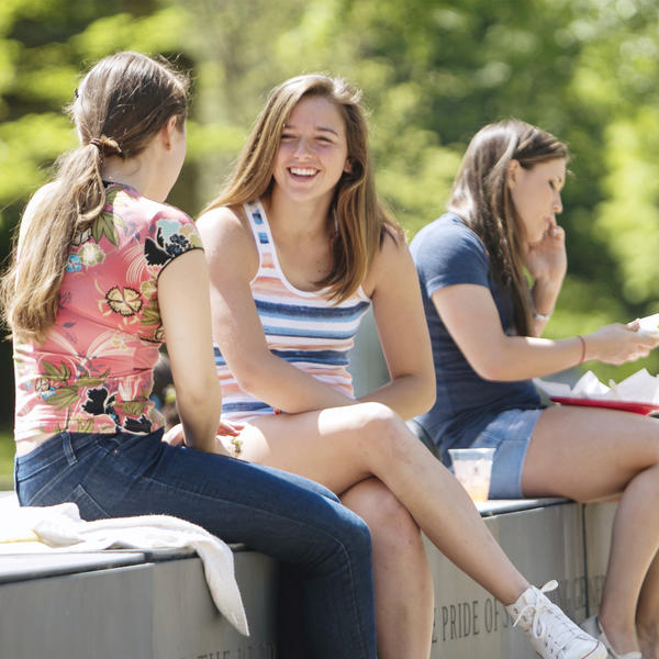 Two women sit on a bench talking and smiling with a third eats her lunch