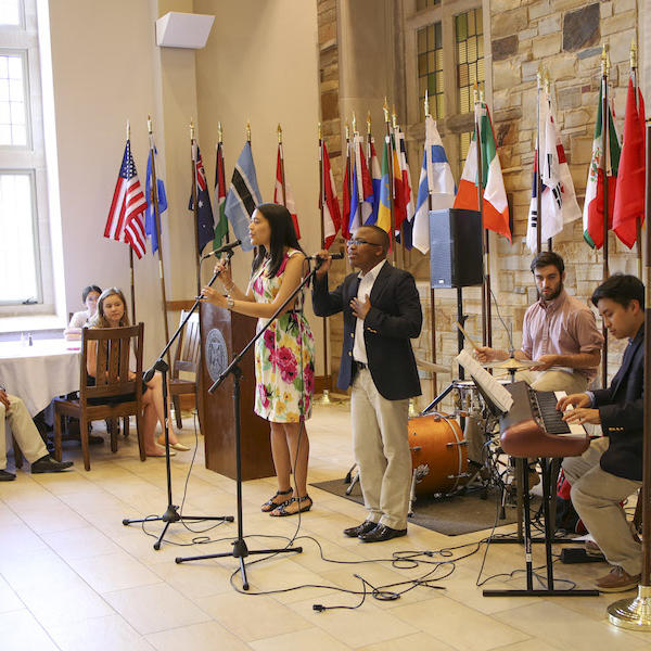 Students playing music in front of an assortment of flags