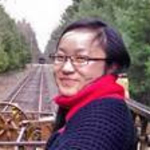 Portrait of Shaolu Yu in front of train tracks surrounded by trees